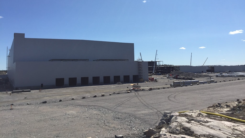 En rad lyftkranar jobbar med att klä in ett stort stålskelett som syns långt bort i bilden bortom en enorm grå fabriksbyggnad som utifrån börjar se klar ut.