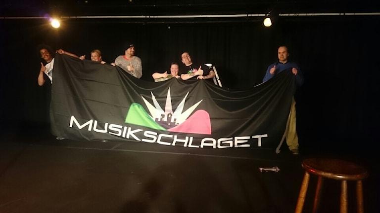 Människor bakom en banderoll som läser 'Musikschlaget'