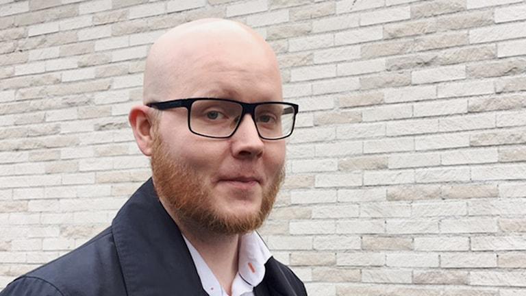 Petter Nilsson Sverigedemokraterna framför en tegelvägg