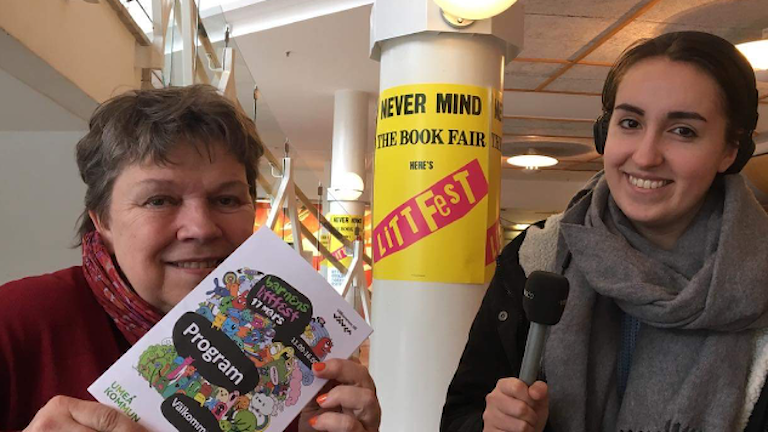 Bibliotekarie Ceceilia Flodström visar affisch för Barnens Littfest för reporter Madeleine Harrati