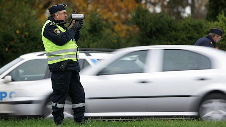 En polis som står med en laserkamera och kontrollerar hastigheten på bilar