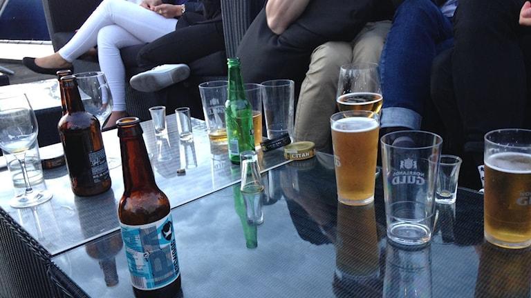 Tomma och fyllda glas på ett soffbord vid en sommarfest utomhus.