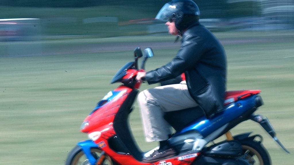 Mopedist kör en röd moped.