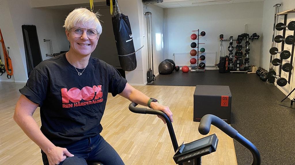 Gymägaren Mona Nilsson i Örnsköldsvik sitter på en motionscykel. Hon har kortklippt ljust hår, glasögon, jeans och svart t-shirt. I bakgrunden syns träningsredskap såsom vikter, bollar och hävstång. Foto: Julia Örtegren/Sveriges Radio