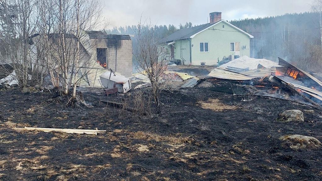 Närmast bilden ser man en svart, bränd gräsyta och längre bak ser man två svedda byggander som det ryker från, den ena av dom har rasat till en hög på marken. Längre bak står ett bostadshus.