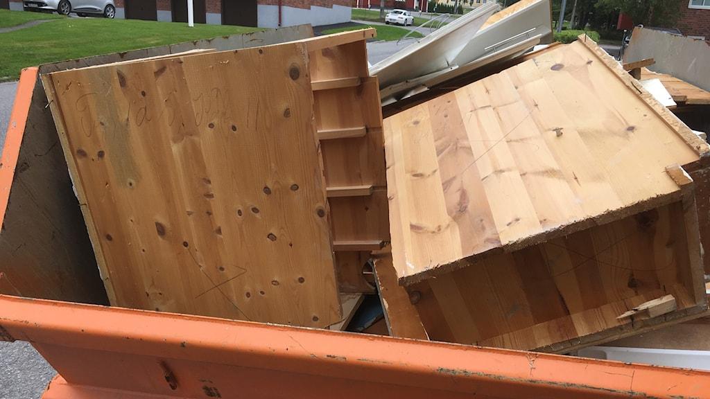 Gamla kasserade möler i sopcontainer, sopor, trasiga möbler