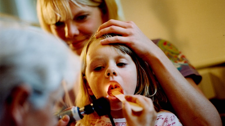 Flicka gapar stort och blir undersökt för halsfluss. Foto: