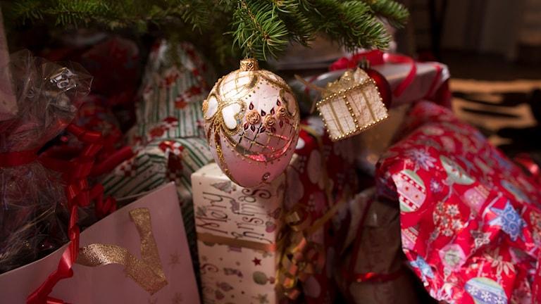 Inslagna julklappar ligger under en pyntad julgran. Foto: Jon Eeg/TT