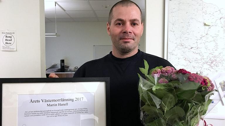 Martin Hanell Årets Västernorrlänning 2017 med diplom och blomsterbukett i handen. Foto: Susanne Helsing/Sveriges Radio