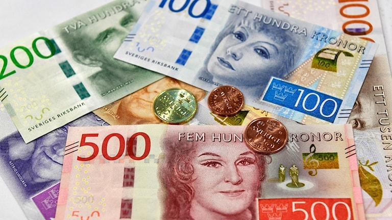 Nya sedlar och mynt upplagda på en bordsskiva.