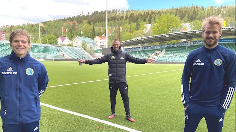 Tre glada fotbollsspelare håller social distans.