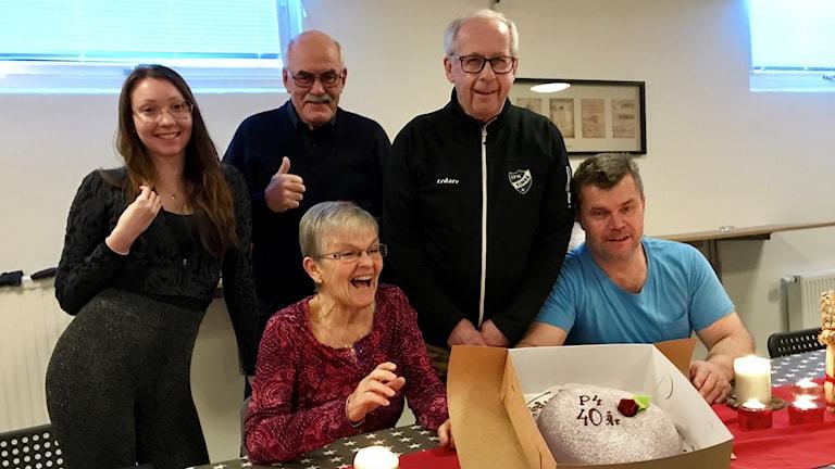 Fem personer redo att hugga in på tårta