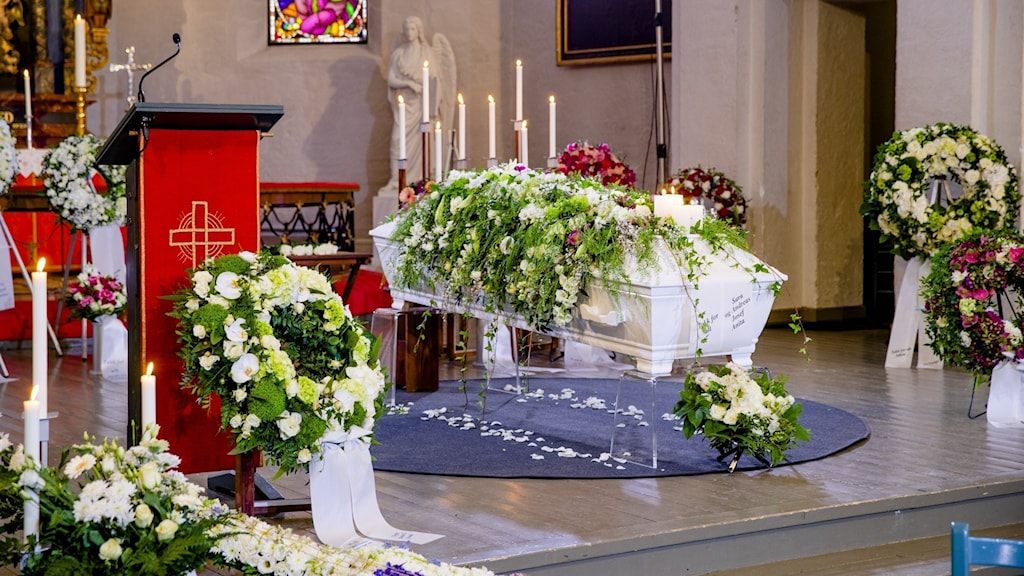 En kista med blomster i kyrkan under en begravningscermoni.