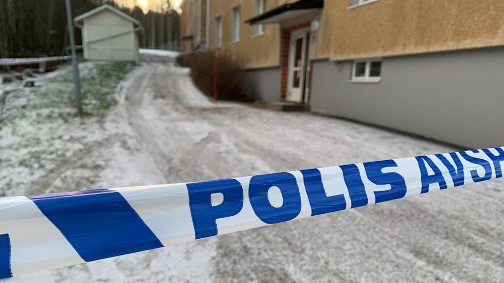 Polisband avspärrat. Lägenhetshus i bakgrunden.