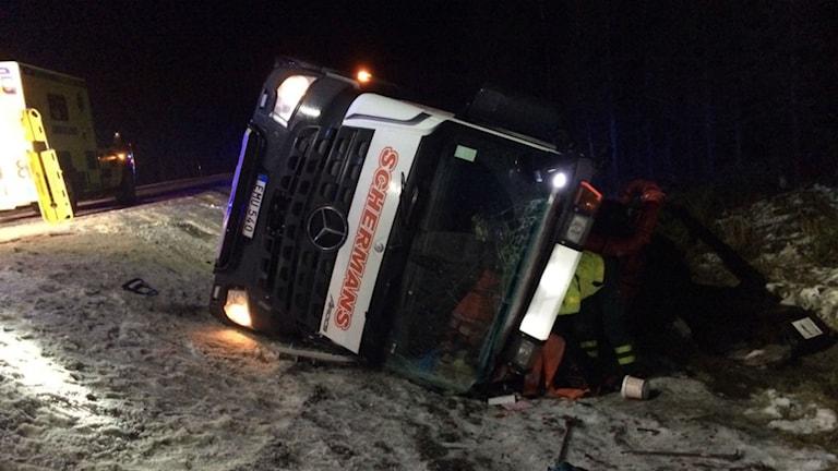 Lastbilen ligger på sidan i diket.