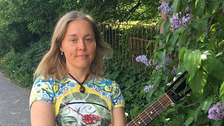 Halvbild på Malin Spjuth med en gitarr vid syrénhäck. Foto: Anna Ahlström/Sveriges Radio