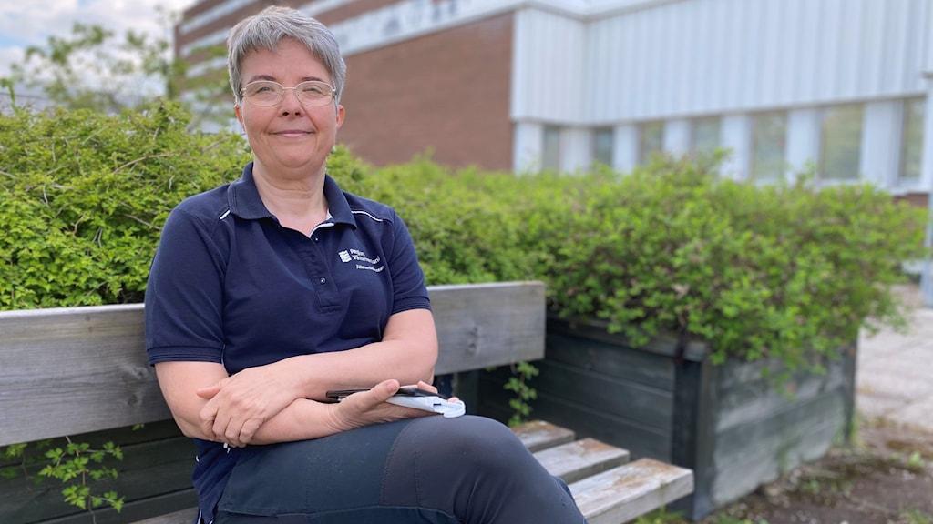 kvinna som sitter på en bänk utanför Sundsvalls sjukhus