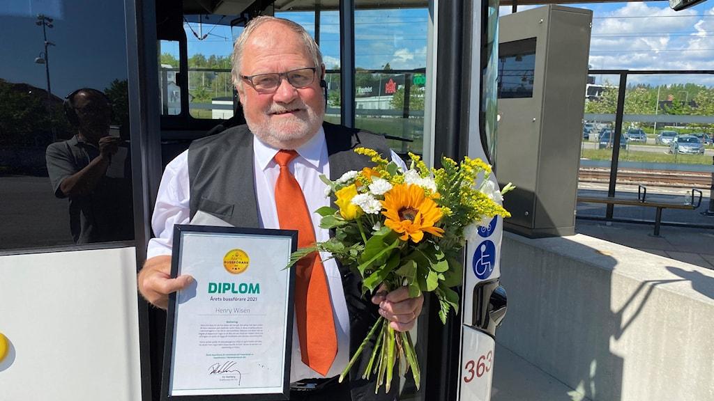 Henry Wisén, årets bussförare står med diplom och blommor framför bussen