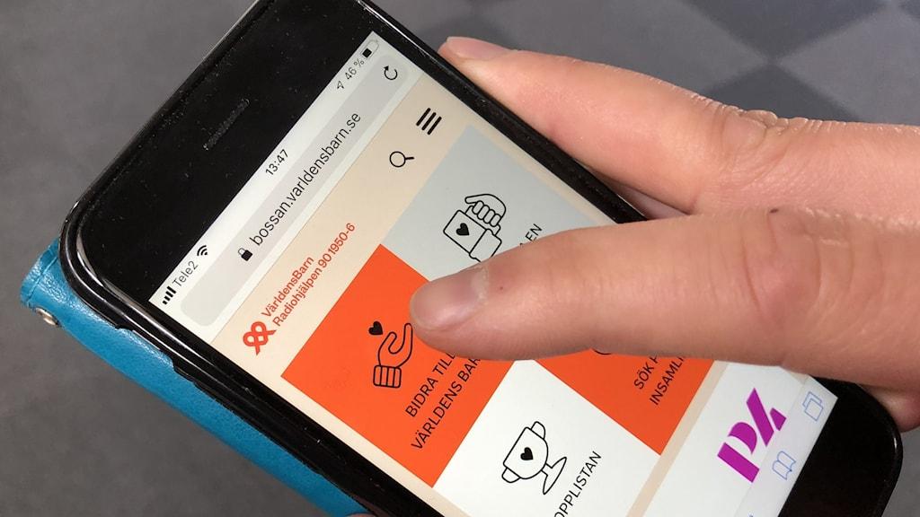 En person skänker pengar till Världens barn med sin mobil genom att trycka på P4 Västernorrlands digitala bössa. Foto: Sveriges Radio