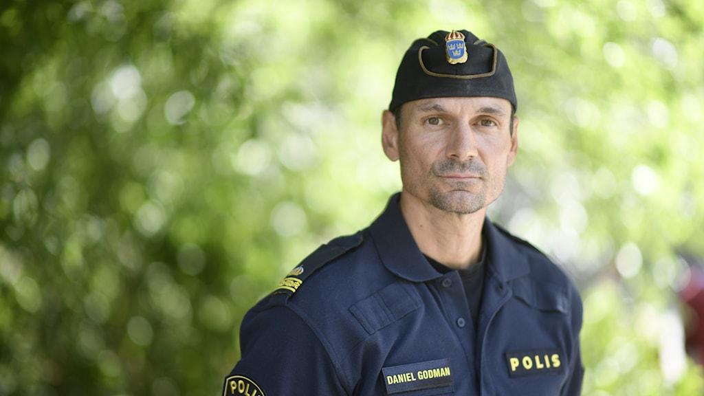 En polis står i uniform bland grönska.