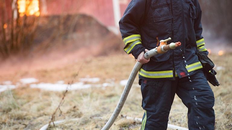 En brandman från räddningstjänsten släcker ett övertänt brinnande hus. I detta fall under en brandövning.
