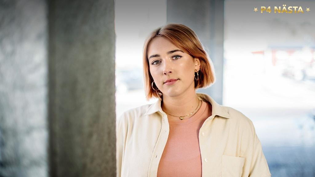 Porträtt av Nina Bring när hon står mellan två  grå betongstolpar. Foto: Petra Berggren