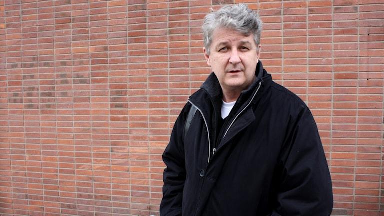 Lennart Eriksson står vid en tegelvägg.