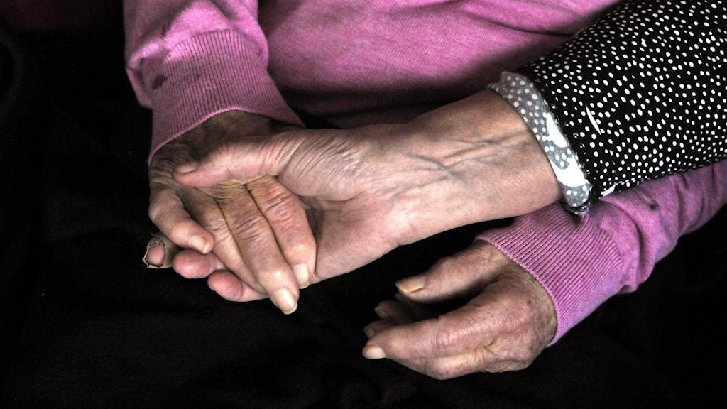 Hand håller äldre kvinnas hand.