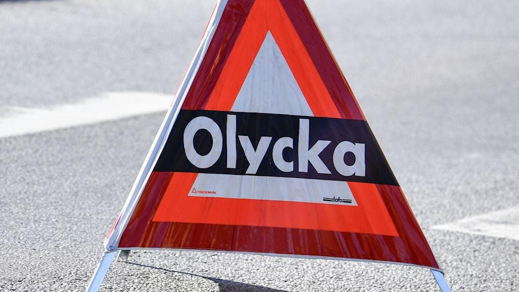 Skylt med texten olycka på en asfaltväg