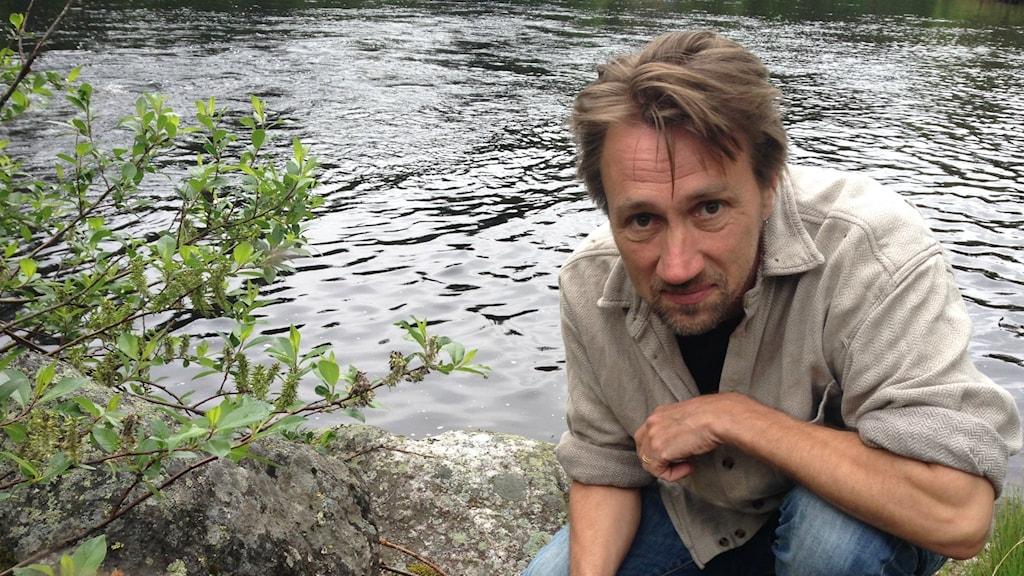 Oskar Norrgrann, biolog och naturvårdhandläggare på Länsstyrelsen Västernorrland sitter på huk bredvid en buske intill Hemlingsån.