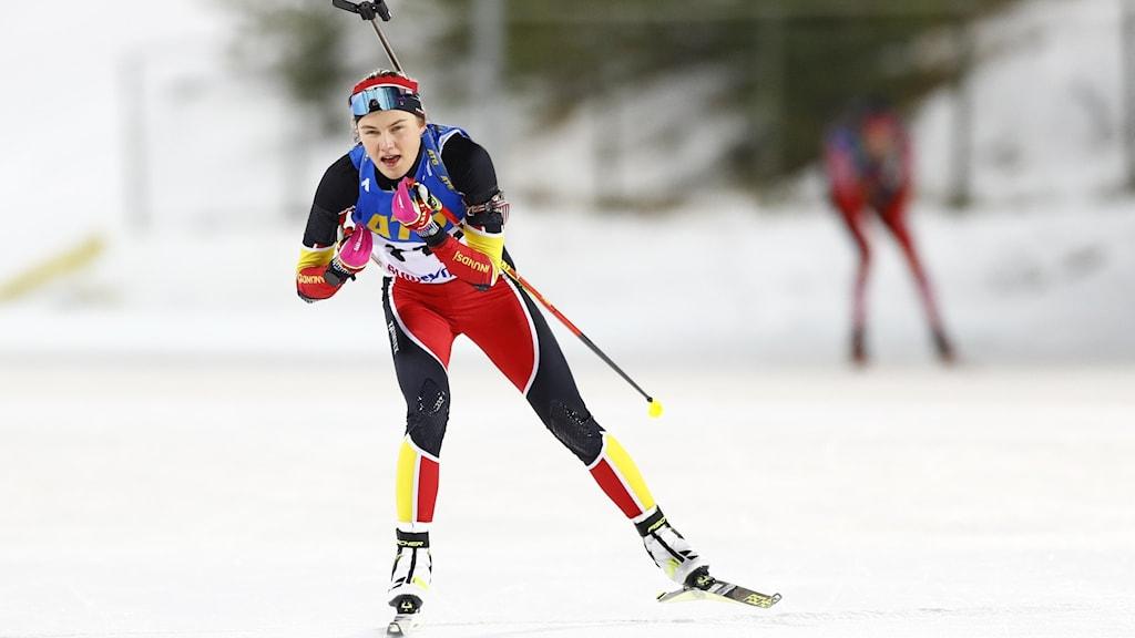 Kvinna med gevär på ryggen och längdskidor i snö