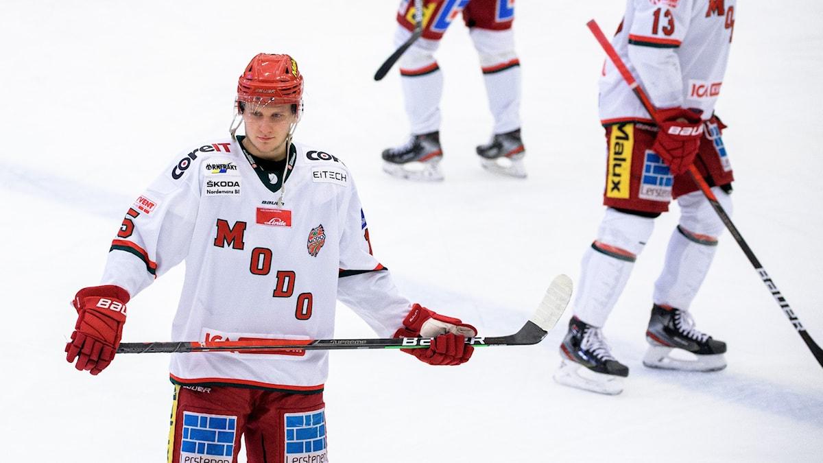 Ishockeyspelare i vit tröja och röda byxor.