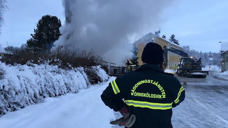 """Man med tryck text på jackan """"Räddningstjänsten Örnsköldsvik"""" tittar på brandplatsen och pratar i mobilen. Foto: Peter Hansson/Sveriges Radio"""