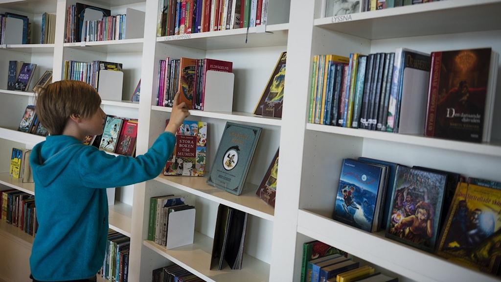 Pojke söker böcker i hylla på bibliotek.