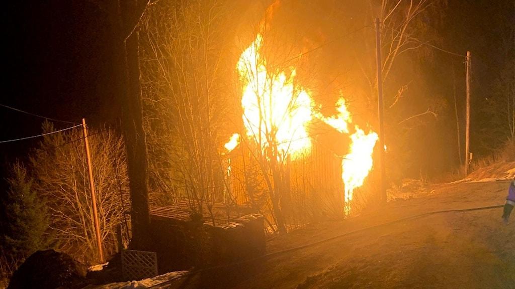 Stora lågor slår ut från det helt övertända huset som var obebott, enligt räddningstjänsten. Foto: Räddningstjänsten Höga Kusten Ådalen