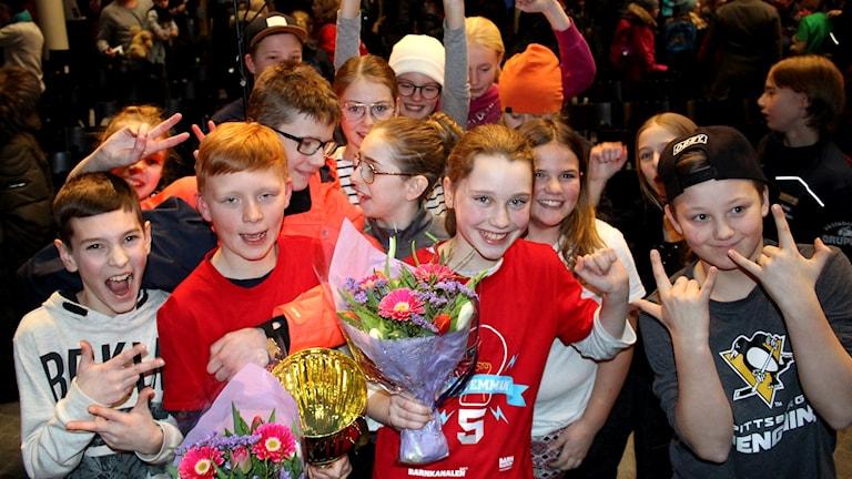 Klassen och laget jublar med pokal och blommor i famnen. Foto: Per-Erik Karlsson/Sveriges Radio