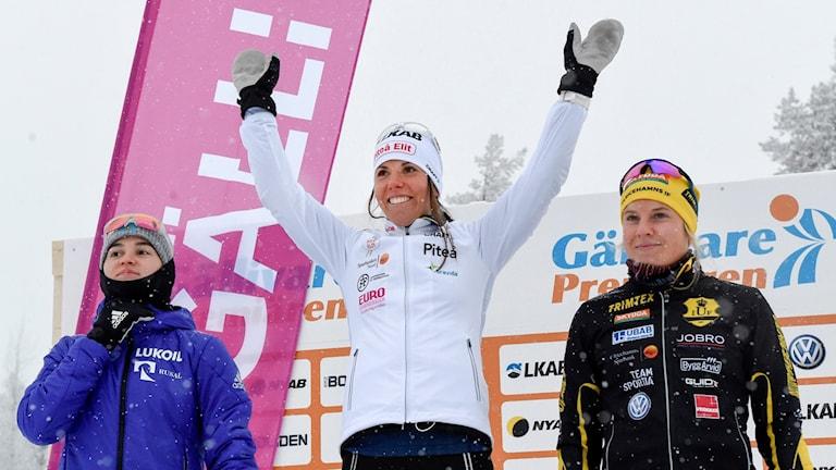 Charlotte Kalla står överst på prispallen i 5 km fri stil i längdskidspremiären. Landslagskollegan Hanna Falk blev tvåa och ryskan Julia Belorukova kom på tredje plats. Foto: Ulf Palm/TT