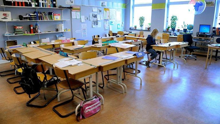 Ensam flicka sitter i en skolbänk i ett klassrum. Foto: Janerik Henriksson / Scanpix