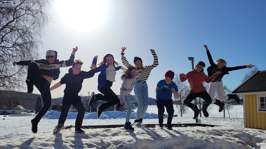 De åtta (!) eleverna i klass 5 på Sidensjöskolan står på en snöhög på skolgården och hoppar upp i luften med armarna i luften. Alla är glada. Foto: Susanna Rönnbäck