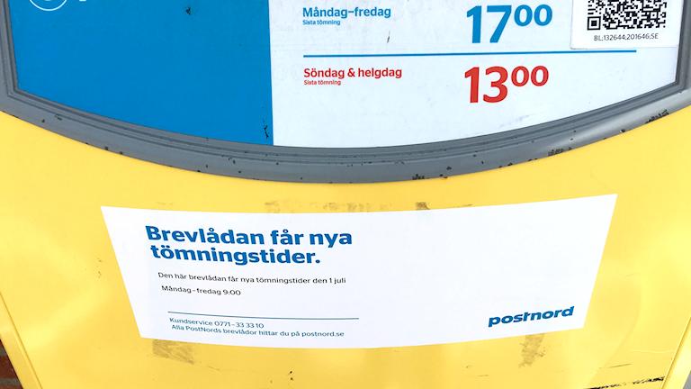 En gul brevlåda, med postnords vit och blåa logga på.
