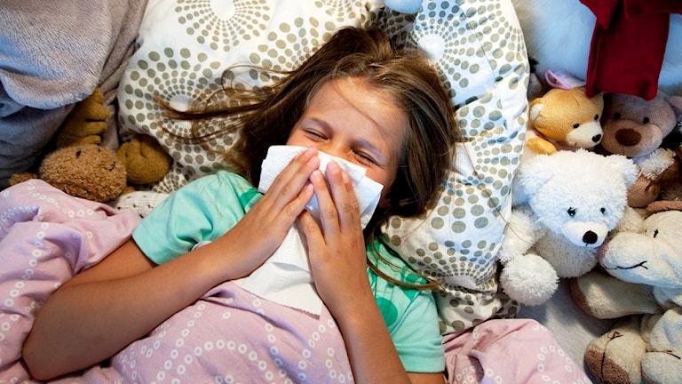 Ett sjukt barn ligger i en säng och snyter sig. Foto: Gorm Kallestad/Scanpix