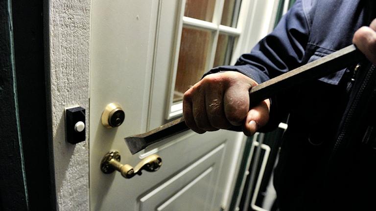 En person bryter sig in genom en vit dörr med en kofot. Foto: Jonas Ekströmer/Scanpix