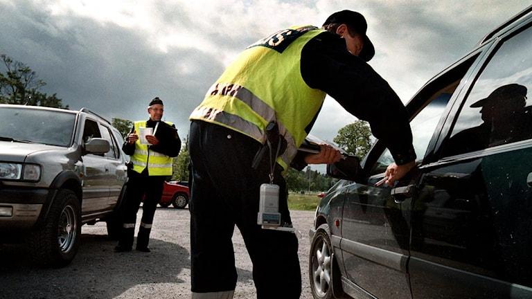 Två poliser kontrollerar två bilar. Foto: Chris Maluszynski/SvD/Scanpix