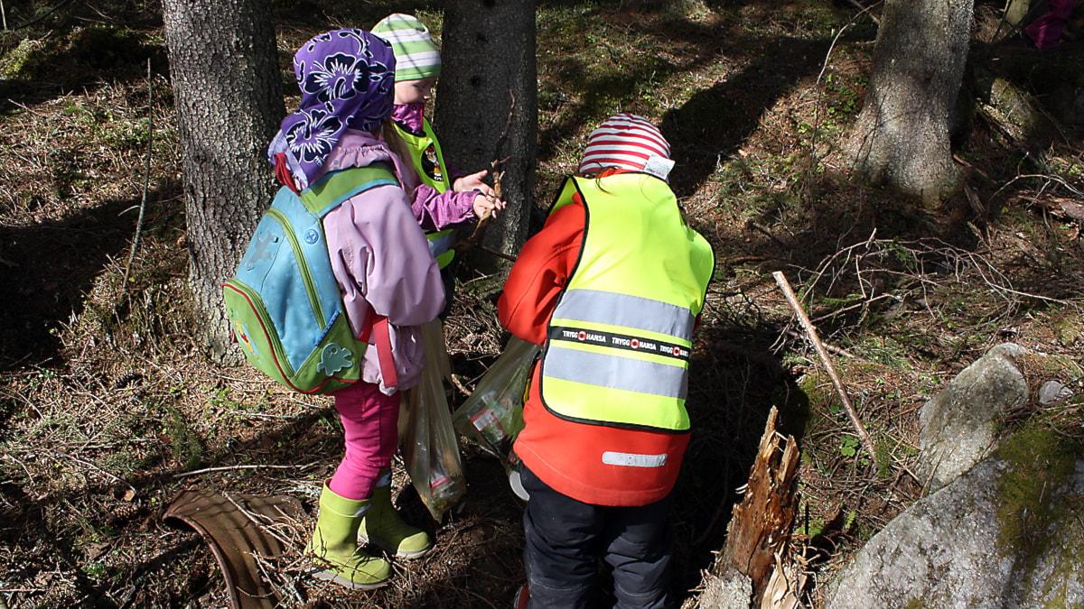 Tre förskolebarn plockar skräp i skogen. Foto: Anna Ahlström