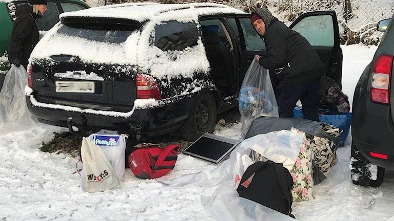 En av EU-migranterna packar ur sina tillhörigheter ur en av bilarna