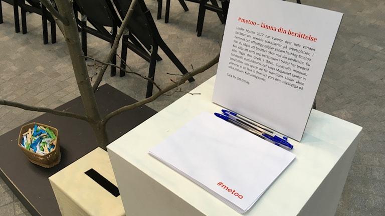 """På en pidistal i mitten av Kulturens hus i Sundsvall ligger papper med texten """"#metoo"""" skrivet i ena hörnet. Bredvid högen med papper ligger pennor och en uppmaning till kvinnor att skriva ner sina berättelser om sexuella övergrepp. Foto: Alexander Arvidsson/Sveriges Radio"""