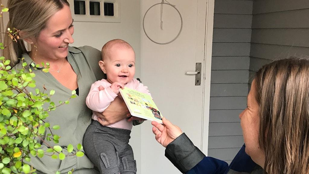 Sex månader gamla Signe får sin första bok av bibliotekarien Helene Lundgren.