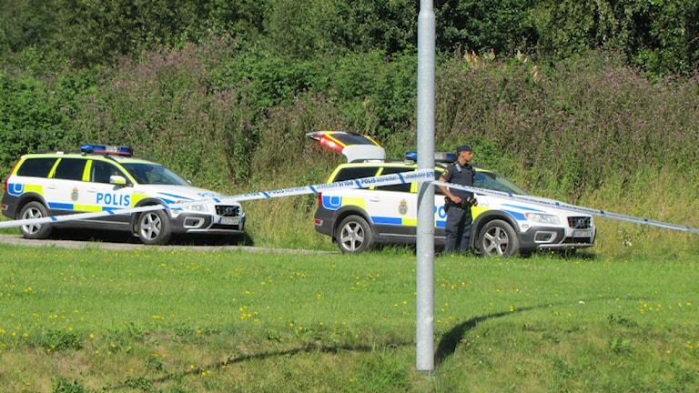 På bilden syns två polisbilar och en polis. Ett större område har blivit avspärrat av polisen efter att en 53-årig kvinna har mördats. Foto: Pontus Hellsén