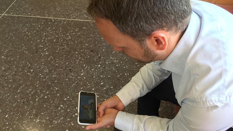 Jörgen Berglund, Moderaternas länsordförande i Västernorrland, tittar på presskonferensen i sin mobil där Anna Kinberg Batra lämnar beskedet att hon lämnar uppdraget som partiledare. Foto: Ingrid Engstedt Edfast/Sveriges Radio