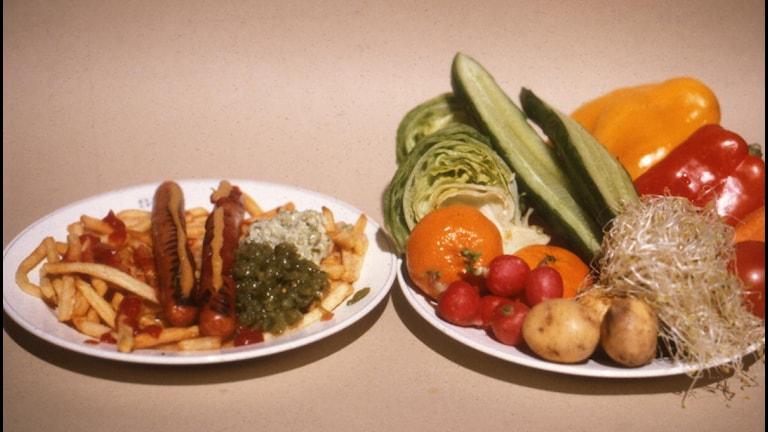En tallrik med grillkorv och pommes frites. En tallrik med grönsaker. Foto: SVT Bild